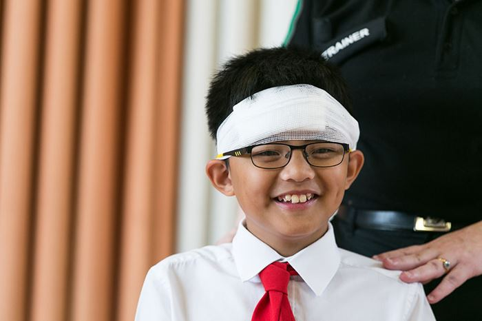 School child smiling with bandage around head