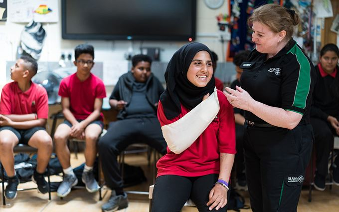 First aid trainer teaching school student