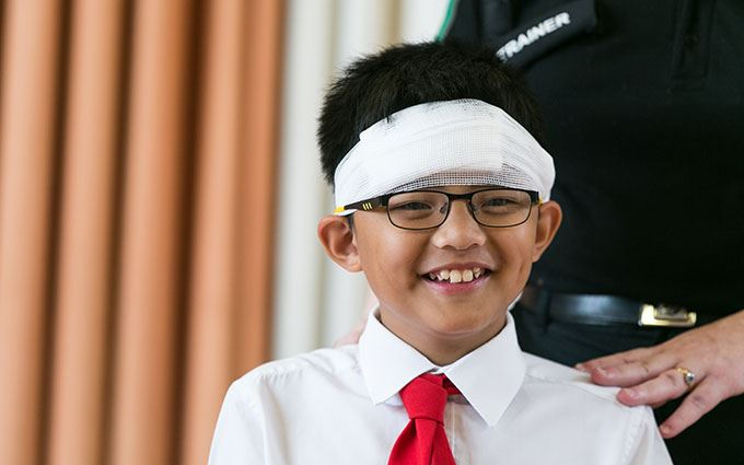 School student learning how to bandage head