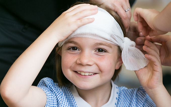 School child with bandage on head