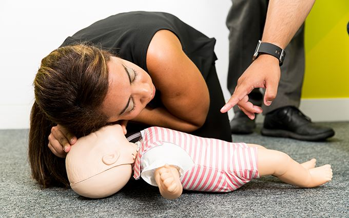 Woman practicing baby resuscitation using a training mannequin