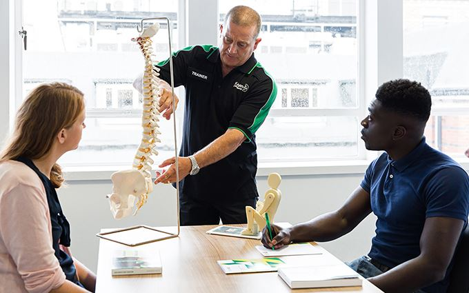 St John Ambulance trainer explaining spinal anatomy to class participants